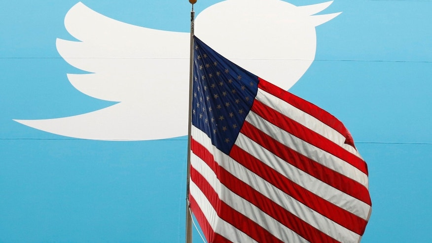The Twitter Inc. logo is shown with the U.S. flag during the company's IPO on the floor of the New York Stock Exchange in New York, November 7, 2013.    REUTERS/Lucas Jackson (UNITED STATES  - Tags: BUSINESS SCIENCE TECHNOLOGY)   - RTX15491