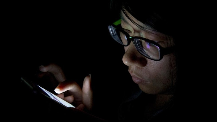 FILE - In this Sept. 11, 2013 file photo, a journalist uses her mobile device during a media event held in Beijing. Beyond setting up passcodes, some phones have additional tools for hiding or securing sensitive photos and documents. (AP Photo/Ng Han Guan, File)