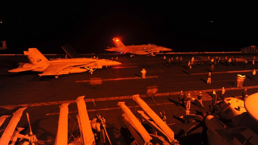 An F/A-18E Super Hornet, attached to Strike Fighter Squadron (VFA) 31, and an F/A-18F Super Hornet, attached to Strike Fighter Squadron (VFA) 213, prepare to launch from the flight deck of the aircraft carrier USS George H.W. Bush (CVN 77) to conduct strike missions against ISIL targets, in the Arabian Gulf.