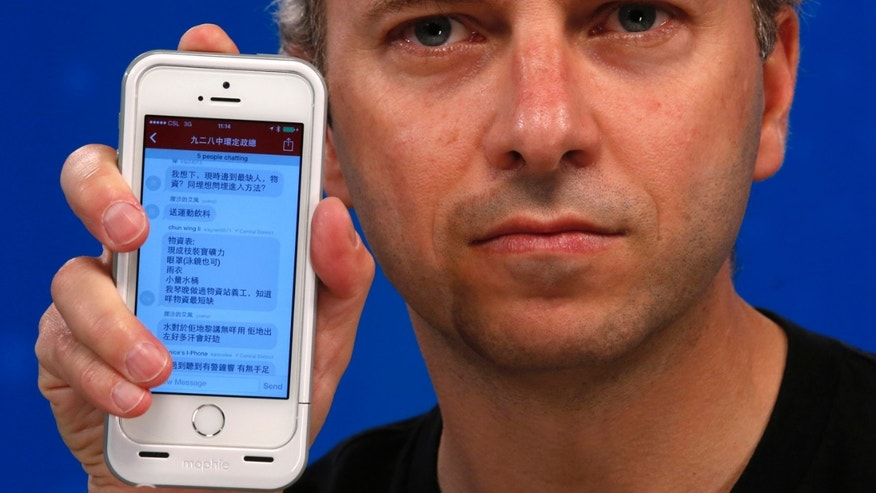 Micha Benoliel, CEO and co-founder of Open Garden, poses with a smartphone displaying the FireChat messaging app during an interview in Hong Kong on October 2.