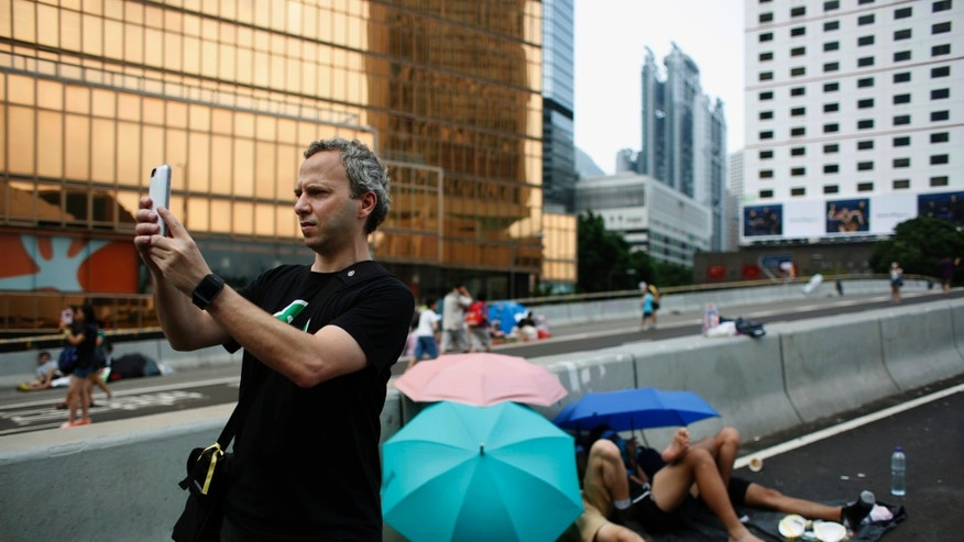 Micha Benoliel, CEO and co-founder of Open Garden, takes a picture on a main road that pro-democracy protesters have blocked at the Central financial district in Hong Kong.
