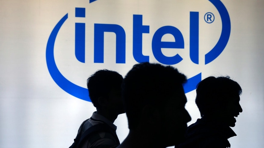 Indonesian youth walk past an Intel sign during Digital Imaging expo in Jakarta March 5, 2014. REUTERS/Beawiharta (INDONESIA - Tags: BUSINESS LOGO SOCIETY) - RTR3G2J1
