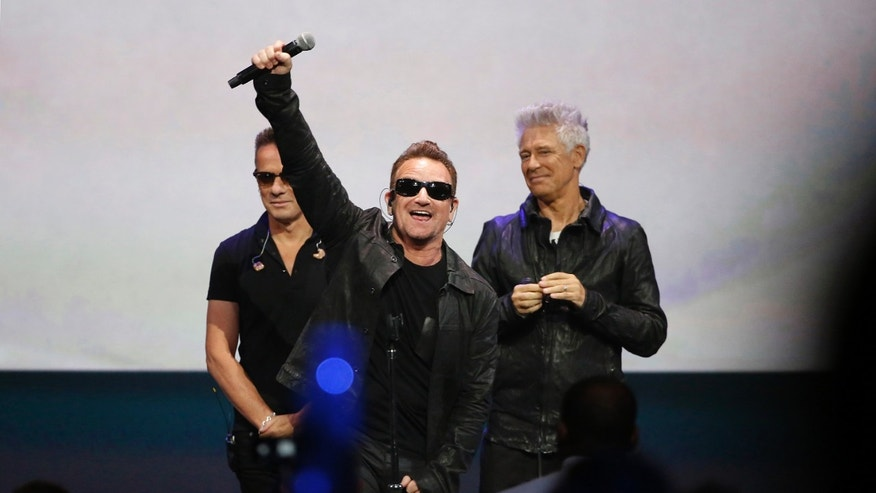 Bono (C) of Irish rock band U2 gestures to the audience after performing at an Apple event at the Flint Center in Cupertino, California, September 9, 2014. REUTERS/Stephen Lam  (UNITED STATES - Tags: BUSINESS ENTERTAINMENT SCIENCE TECHNOLOGY TPX IMAGES OF THE DAY) - RTR45LHD