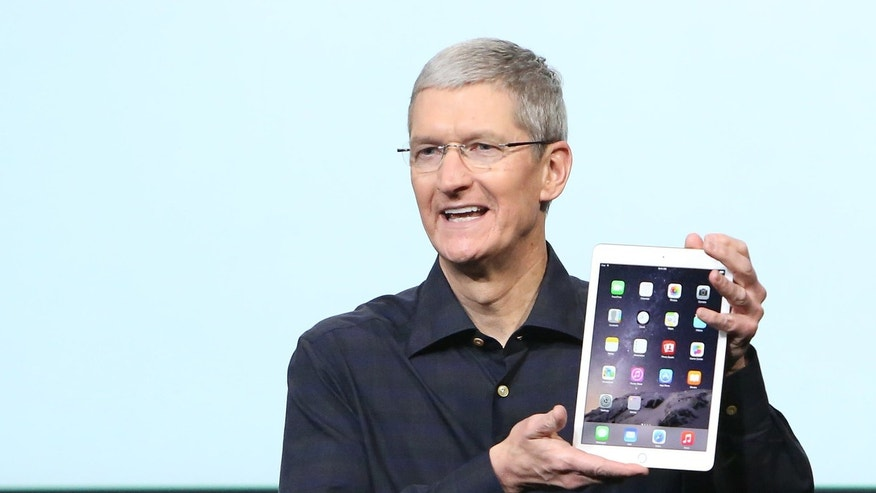 Apple CEO Tim Cook holds an iPad during a presentation at Apple headquarters October 16, 2014.
