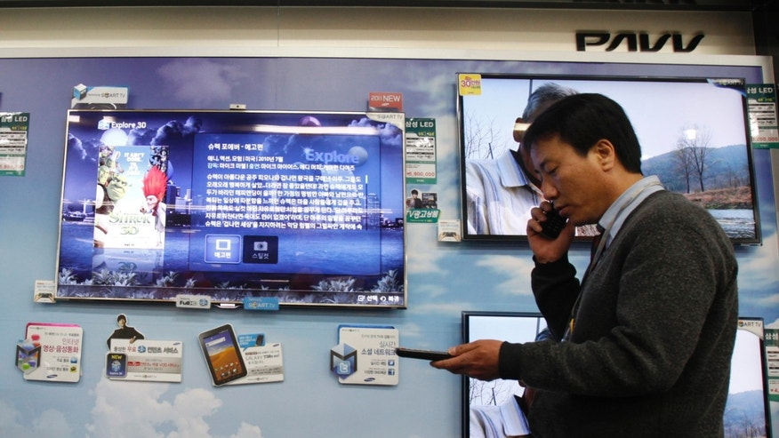 A salesman talks on his mobile phone as he walks past Samsung Electronics's LED television displays at an electronics store in Seoul.