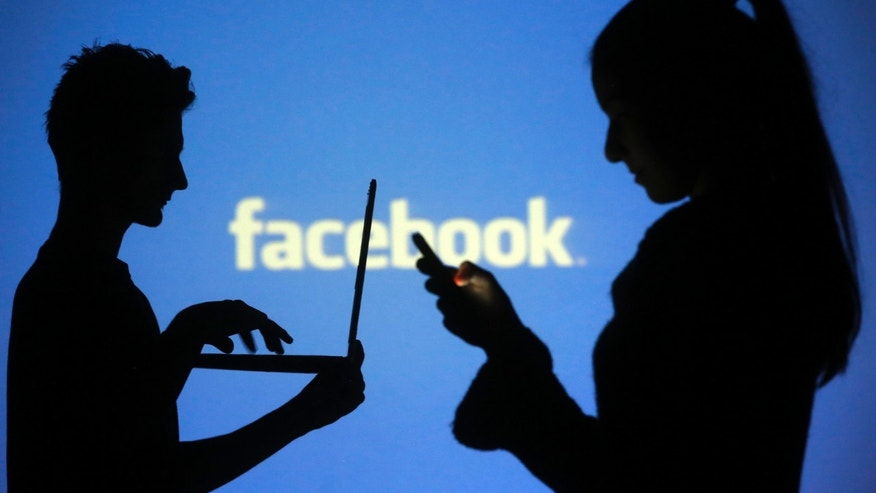 People are silhouetted as they pose with laptops in front of a screen projected with a Facebook logo, in this picture illustration taken in Zenica October 29, 2014. Facebook Inc warned on Tuesday of a dramatic increase in spending in 2015 and projected a slowdown in revenue growth this quarter, slicing a tenth off its market value. Facebook shares fell 7.7 percent in premarket trading the day after the social network announced an increase in spending in 2015 and projected a slowdown in revenue growth this quarter.  REUTERS/Dado Ruvic (BOSNIA AND HERZEGOVINA  - Tags: BUSINESS SCIENCE TECHNOLOGY BUSINESS LOGO)   - RTR4C0V2