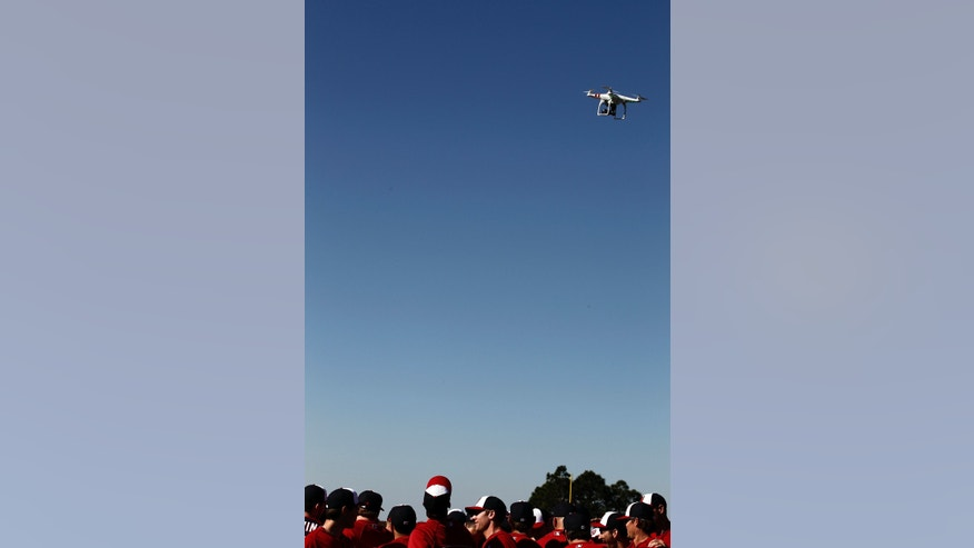 FILE - A remote controlled model aircraft flies over the Washington Nationals spring training baseball workout in Viera, Fla.