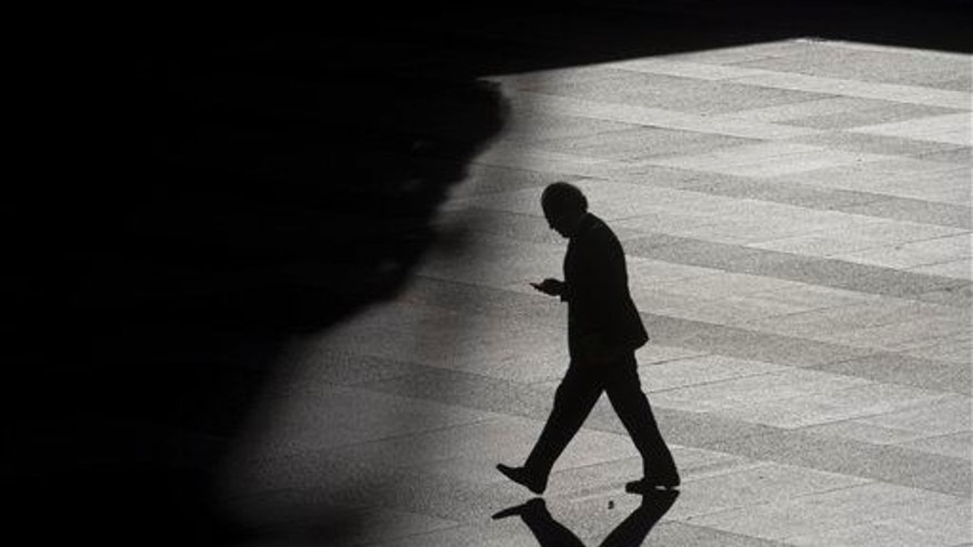 A man looks as his cell phone as he walks into the shadows.