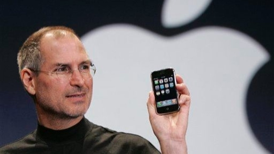 Apple CEO Steve Jobs holds up an Apple iPhone at the Macworld conference in San Francisco on Jan. 9, 2007.