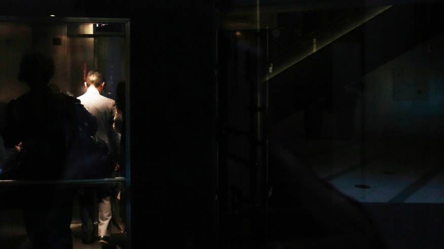 File photo - a man rides on an elevator inside a building in Tokyo.
