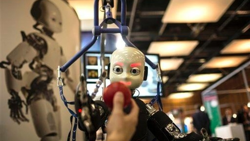This March 19, 2013, file photo shows the iCub robot trying to catch a ball.The iCub robot is used for research into artificial intelligence.
