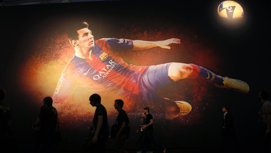 "Visitors walk past a placard of ""FIFA 15"" video game featuring soccer player Lionel Messi at the Gamescom 2014 fair in Cologne Aug. 13, 2014."