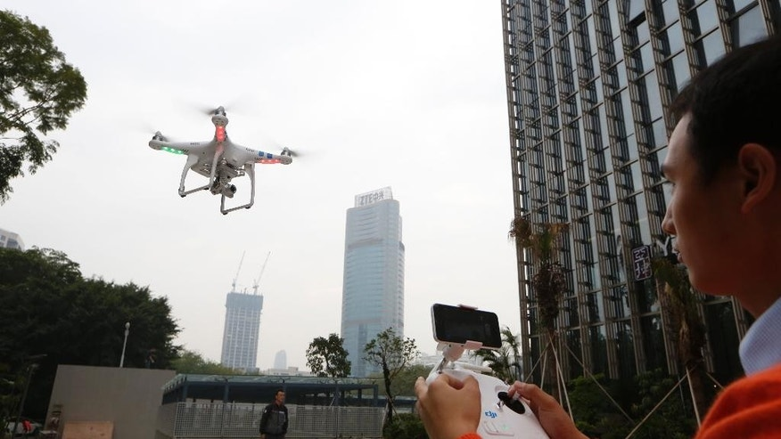 In this Monday, Dec. 15, 2014 photo, a staff member from DJI Technology Co. demonstrates the remote flying with his Phantom 2 Vision+ drone in Shenzhen, south China's Guangdong province. Founded in 2009 by an engineer with a childhood love of radio-controlled model planes, DJI has become the leading supplier in the fast-growing market for civilian drones - possibly the first Chinese brand to achieve No. 1 status in a global consumer product. (AP Photo/Kin Cheung)