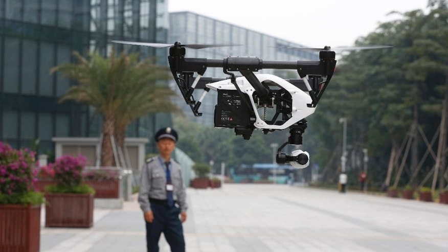 In this Monday, Dec. 15, 2014 photo, a security guard watches a demonstration of a DJI Technology Co. Inspire 1 drone in Shenzhen, south China's Guangdong province. Founded in 2009 by an engineer with a childhood love of radio-controlled model planes, DJI has become the leading supplier in the fast-growing market for civilian drones - possibly the first Chinese brand to achieve No. 1 status in a global consumer product. (AP Photo/Kin Cheung)
