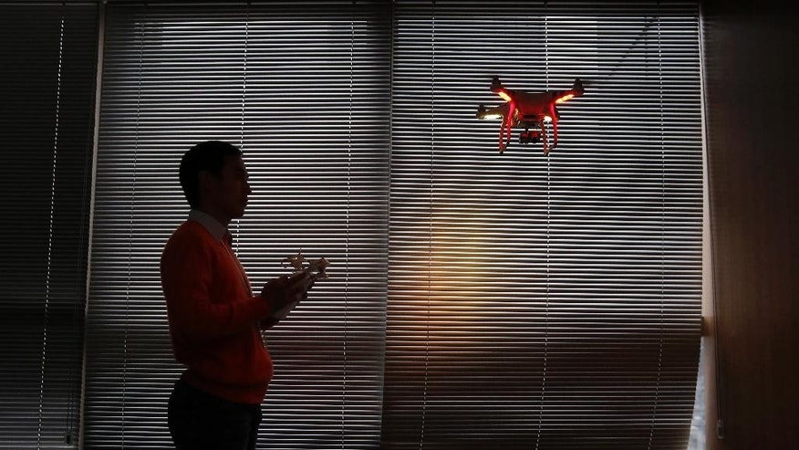 In this Monday, Dec. 15, 2014 photo, a staff member from DJI Technology Co. demonstrates the remote flying with his Phantom 2 Vision+ drone inside his office in Shenzhen, south China's Guangdong province. Founded in 2009 by an engineer with a childhood love of radio-controlled model planes, DJI has become the leading supplier in the fast-growing market for civilian drones - possibly the first Chinese brand to achieve No. 1 status in a global consumer product. (AP Photo/Kin Cheung)