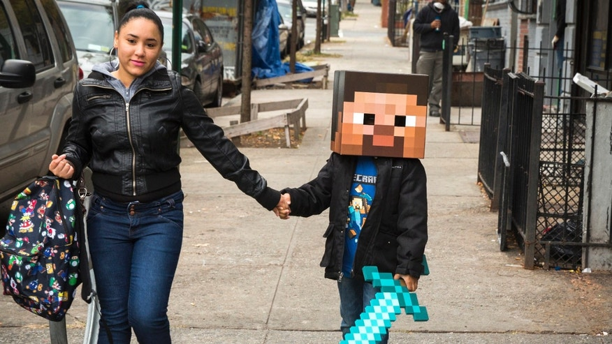 A woman walks her child to school as he is dressed as a character from Minecraft in New York October 31, 2014.