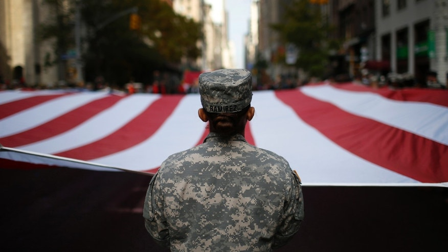 File photo - U.S. Army soldiers carry a large U.S. flag as they march in the Veterans Day parade on 5th Avenue in New York Nov. 11, 2014.
