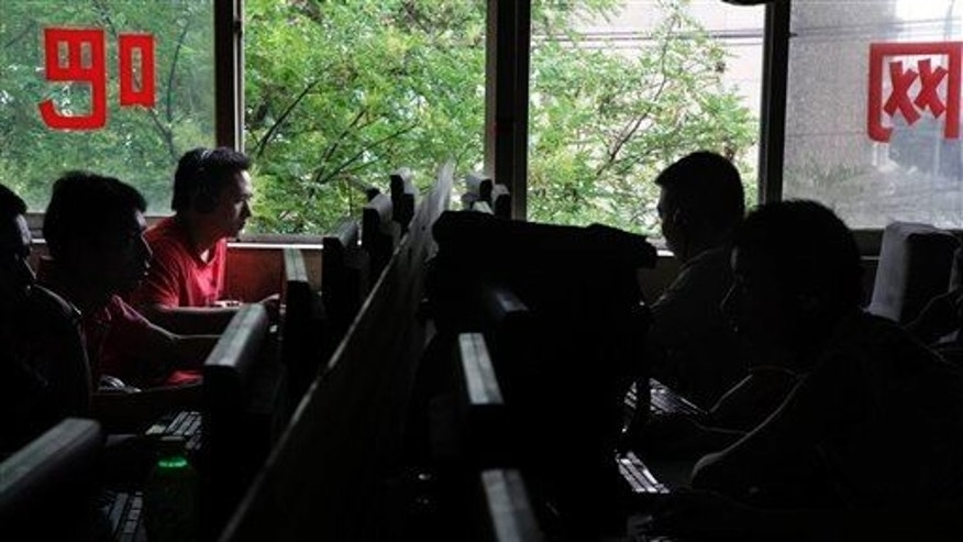 Chinese computer users sits in front of computer terminals at an Internet cafe in Beijing, China, Wednesday, July 14, 2010.