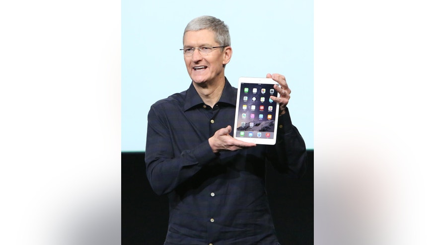 Apple CEO Tim Cook holds an iPad during a presentation at Apple headquarters in Cupertino, California Oct. 16, 2014.
