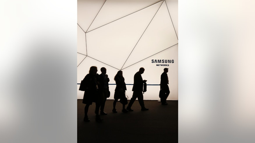 People walk past a Samsung stand while attending the Mobile World Congress in Barcelona March 2, 2015.