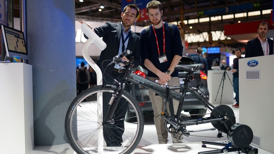 A worker shows a visitor the e-bike from Ford at the Mobile World Congress.