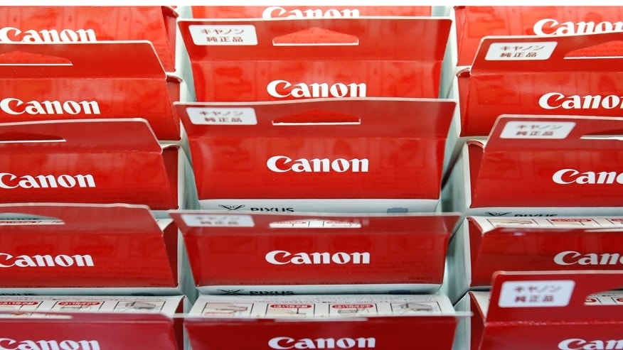 File photo. Canon's logos are pictured on printer ink packages displayed at an electronics retail store in Tokyo.