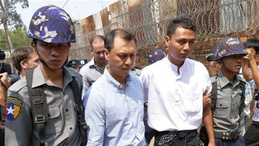 V Gastro bar owner Tun Thurein, second from left, and employee Htut Ko Ko Lwin, second from right, are escorted by Burma police officers at a township court Tuesday, March 17, 2015, in Yangon.