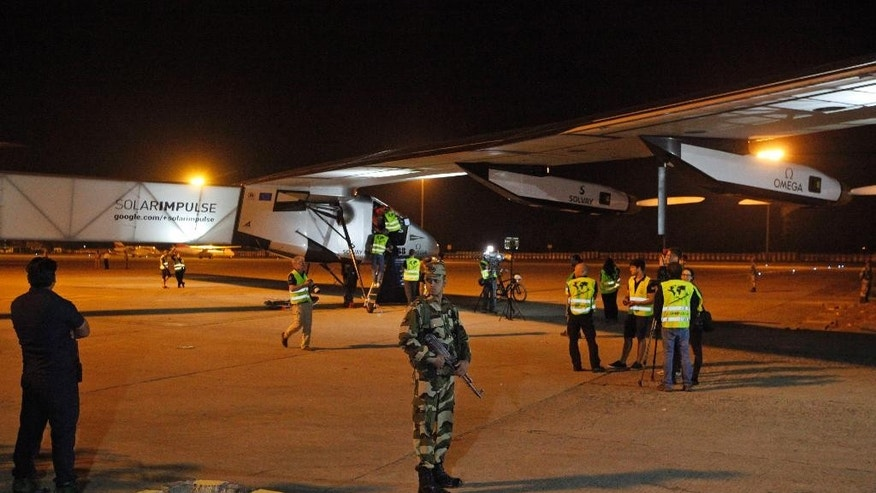 An Indian security man guards as Swiss-made Solar Impulse-2 prepares to take off from Ahmadabad, India, Wednesday, March 18, 2015. The solar powered aircraft is Wednesday headed to the northern Indian city of Varanasi on the third leg of its' historic round-the-world trip. (AP Photo/Ajit Solanki)