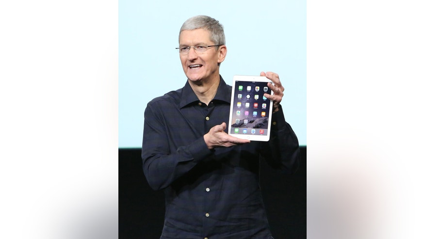 Apple CEO Tim Cook holds an iPad during a presentation at Apple headquarters in Cupertino, Calif. Oct. 16, 2014.