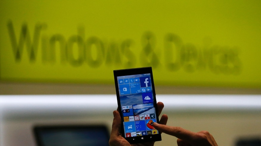 A Microsoft representative shows a smartphone with Windows 10 operating system at the CeBIT trade fair in Hanover March 15, 2015.