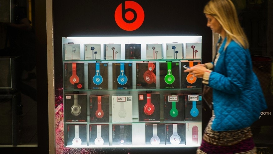 A pedestrian walks past a Beats brand display in the subway system of New York, May 29, 2014.