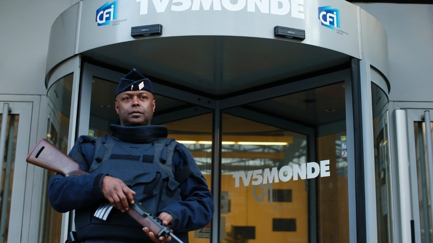 A French police officer stands guard in front of the main entrance of French television network TV5Monde headquarters in Paris April 9, 2015.