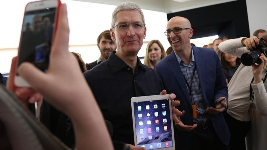 File photo. Apple CEO Tim Cook holds a new iPad after a presentation at Apple headquarters in Cupertino, California October 16, 2014.