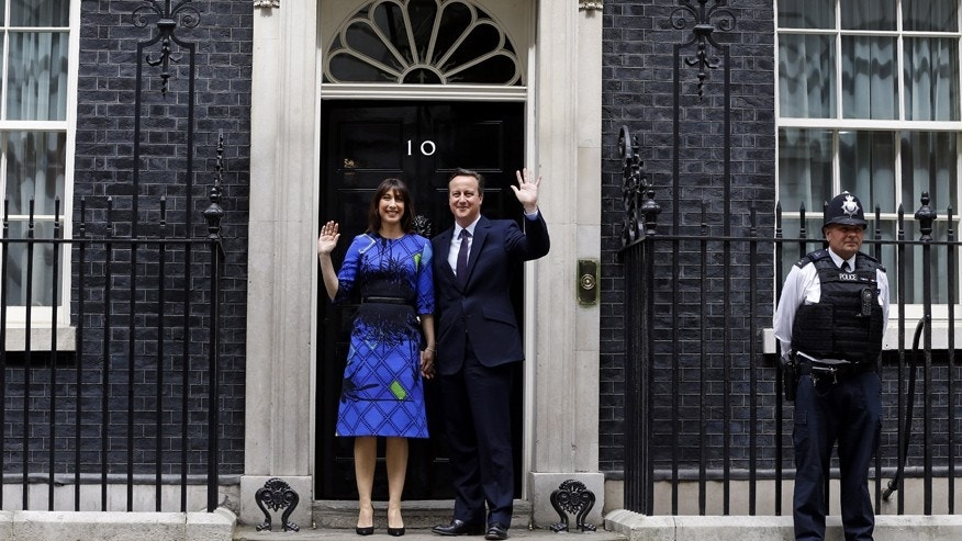 Britain's Prime Minister David Cameron and his wife Samantha wave from the steps of 10 Downing Street in London Friday, May 8, 2015.