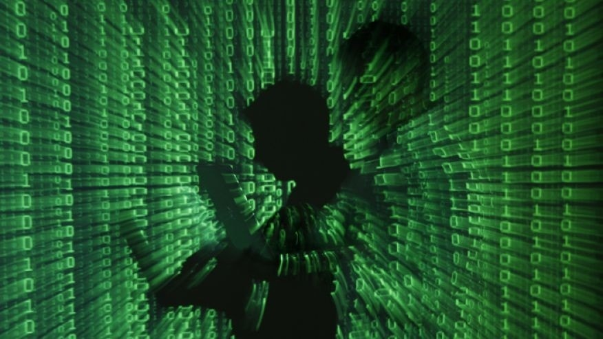 Photo illustration shows projection of binary code on a man holding a laptop computer. (Reuters)