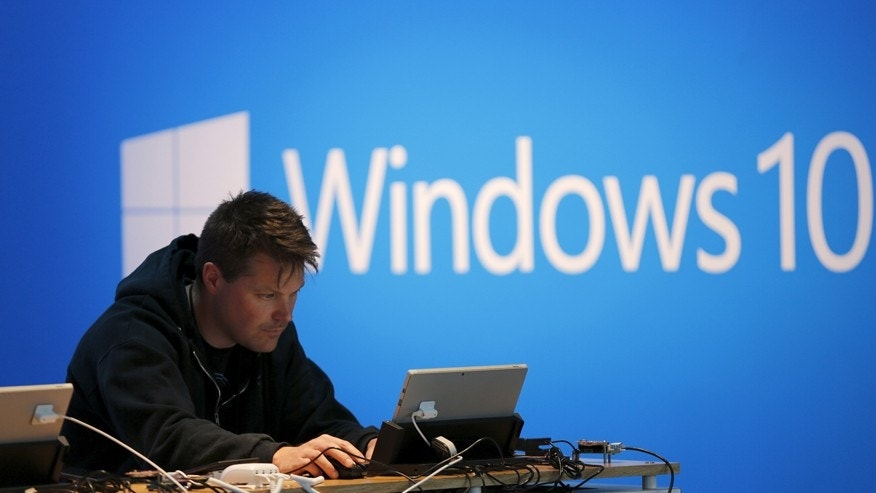 A man works on a laptop computer near a Windows 10 display at Microsoft Build in San Francisco, California April 29, 2015.