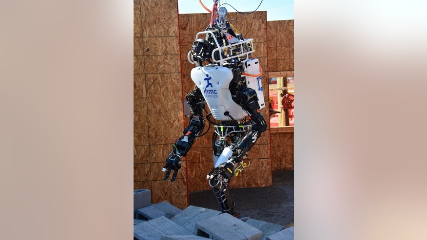 Florida's Institute of Human and Machine Cognition team robot, Running Man, makes its way over a field of rubble during a test event.