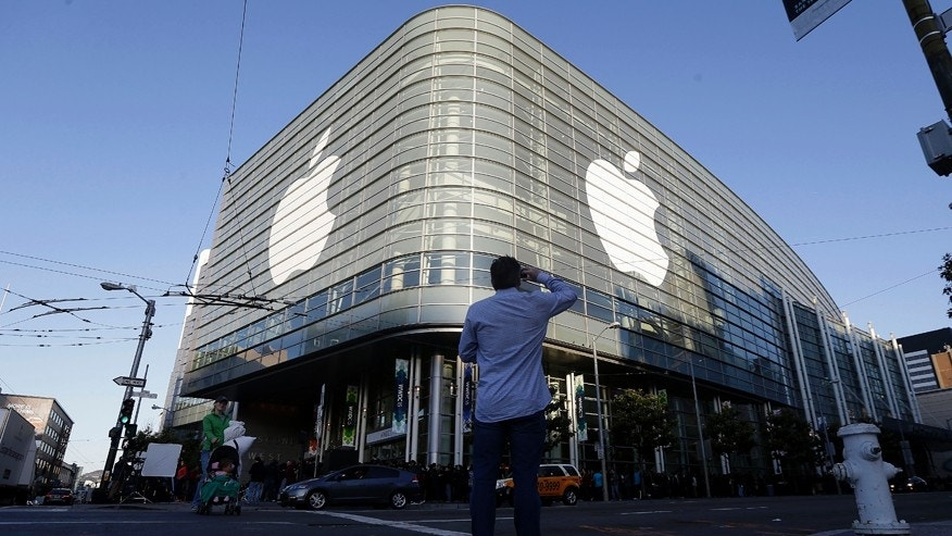 Apple logos adorn the exterior of the Moscone West building on the first day of the Apple Worldwide Developers Conference in San Francisco, Monday, June 8, 2015.