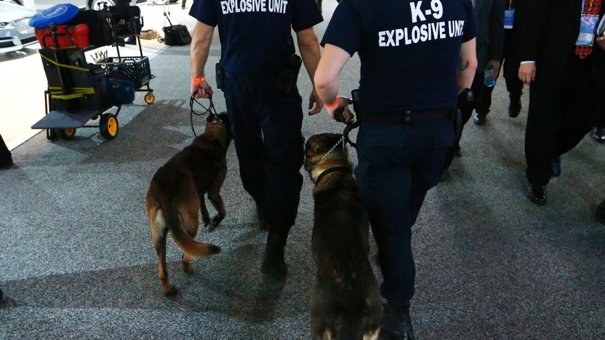 File photo. Two police officers guide bomb-sniffing dogs past exhibits during the second press day of the North American International Auto Show in Detroit, Michigan, January 13, 2015.