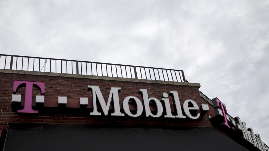 File photo - People pass by a T-Mobile store in the Brooklyn borough of New York June 4, 2015.