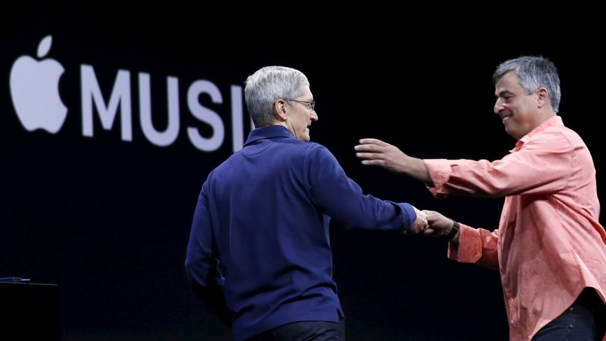 File photo. Apple CEO Tim Cook (L) greets senior vice president of internet services and software Eddy Cue during his keynote address at the Worldwide Developers Conference in San Francisco, California June 8, 2015.