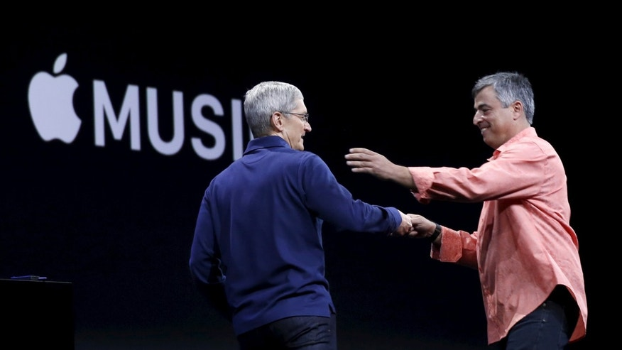 Apple CEO Tim Cook (L) greets senior vice president of internet services and software Eddy Cue during his keynote address at the Worldwide Developers Conference in San Francisco, California June 8, 2015.