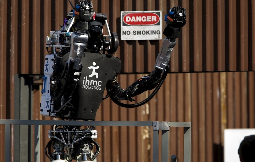 "The Team IHMC Robotics Atlas ""Running Man"" robot built by Boston Dynamics raises its arms to celebrate after climbing the stairs during the finals of the Defense Advanced Research Projects Agency (DARPA) Robotic Challenge in Pomona, California June 6, 2015."