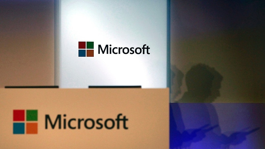 File photo - A shadow of a man using his mobile phone is cast near Microsoft logo at the 2014 Computex exhibition in Taipei June 4, 2014.