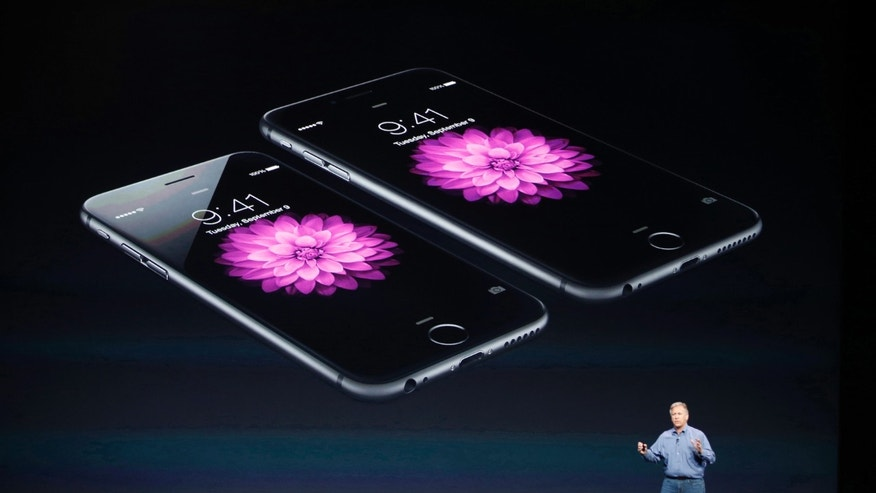 Phil Schiller, Senior Vice President at Apple Inc., speaks about the iPhone 6 (foreground) and the iPhone 6 Plus during an Apple event at the Flint Center in Cupertino, Calif., Sept. 9, 2014.