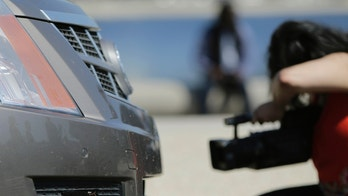File photo. A member of the media photographs the front end sensors of a 2011 Cadillac SRX autonomous car created by students and staff of Carnegie Mellon University in Washington June 24, 2014.