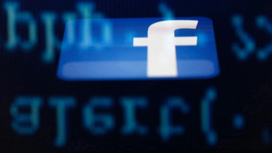 A Facebook logo on an Ipad is reflected among source code on the LCD screen of a computer, in this photo illustration taken in Sarajevo June 18, 2014.