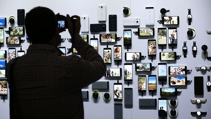 A reporter takes a picture of new Google devices on display during a Google event on Tuesday, Sept. 29, 2015, in San Francisco.