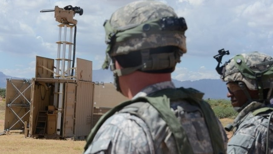 Lt. Col. Raphael Heflin, right, commander, 142nd Combat Service Support Battalion, 1st Armored Division, and another Soldier pass near a remotely-controlled weapons system.
