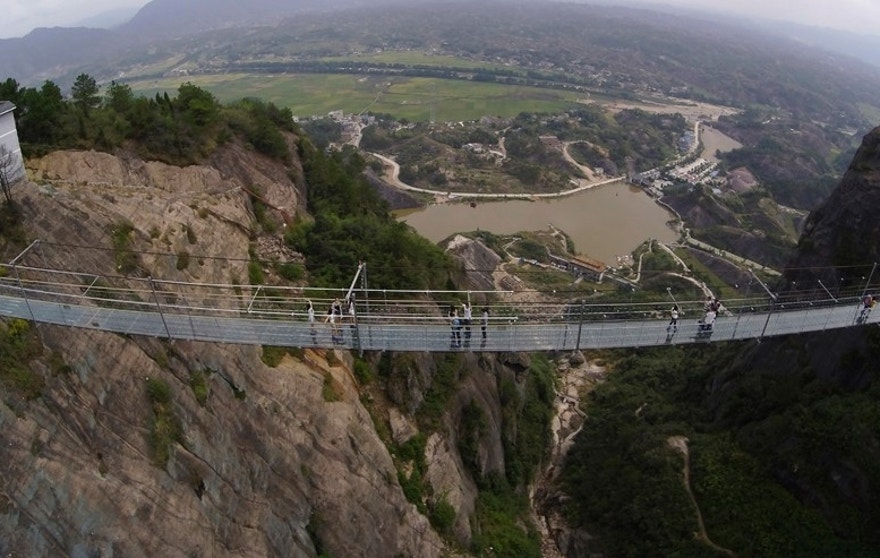 Visitors walk across a glass-bottomed suspension bridge as seen from the air in a scenic zone in Pingjiang county in southern China's Hunan province Thursday, Sept. 24, 2015. The bridge, 300 meters (984 feet) long and 180 meters (590 feet) above the valley floor, opened to visitors on Thursday for the first time since its conversion from a regular suspension bridge was completed. (Chinatopix Via AP) CHINA OUT